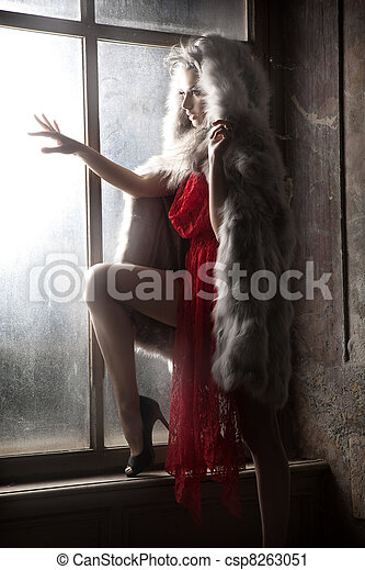Sexy woman as a red hood looking out window - csp8263051