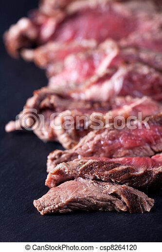 sliced sirloin steak on a slate - csp8264120