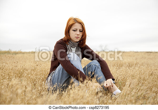 Lonely sad red-haired girl at field - csp8273195