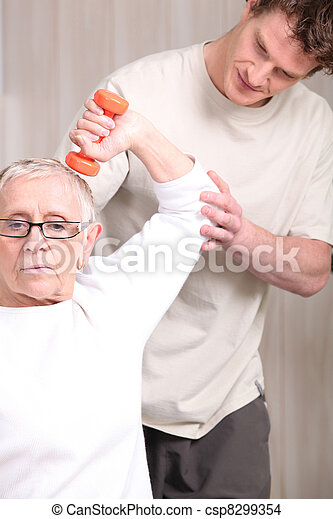 Sports coach and senior woman with dumbbell