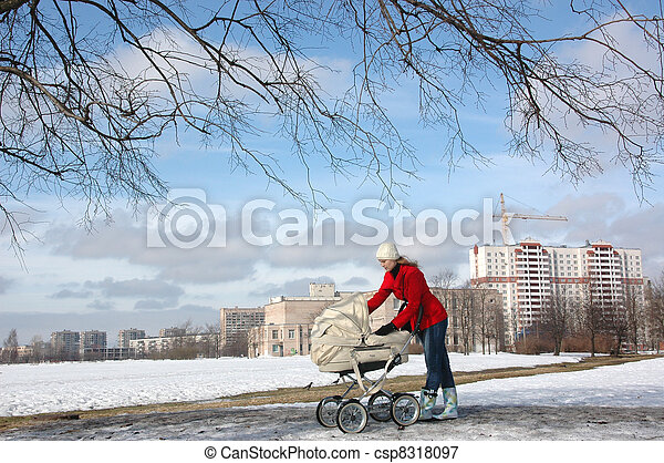 Wide shot of happy young mother in red coat with baby in buggy walking in winter park - csp8318097