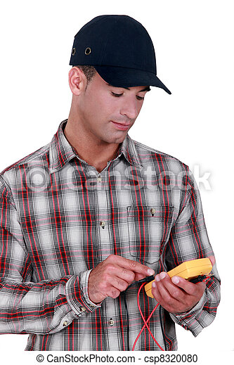 young electrician wearing cap using tester - csp8320080