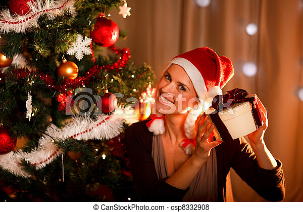 Interested woman near Christmas tree shaking present box trying to guess what\'s inside