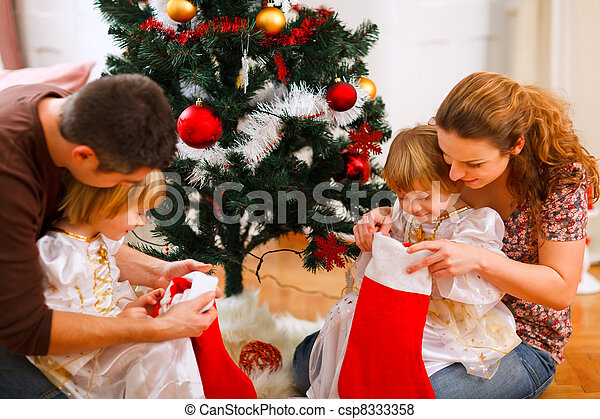 Mom and dad looking with twins daughters inside of Christmas socks near Christmas tree