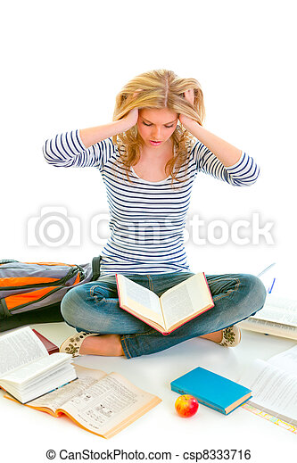 Teen girl sitting on floor among schoolbooks and studying hard - csp8333716