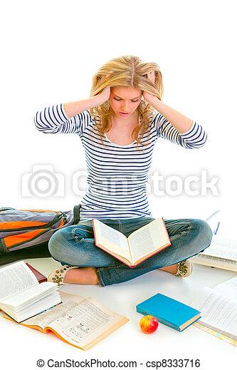 Teen girl sitting on floor among schoolbooks and studying hard - csp8333716