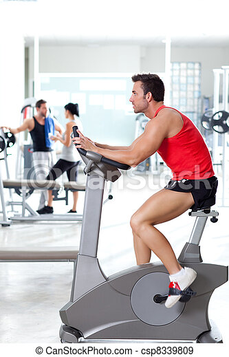man on stationary bicycle at sport fitness gym - csp8339809