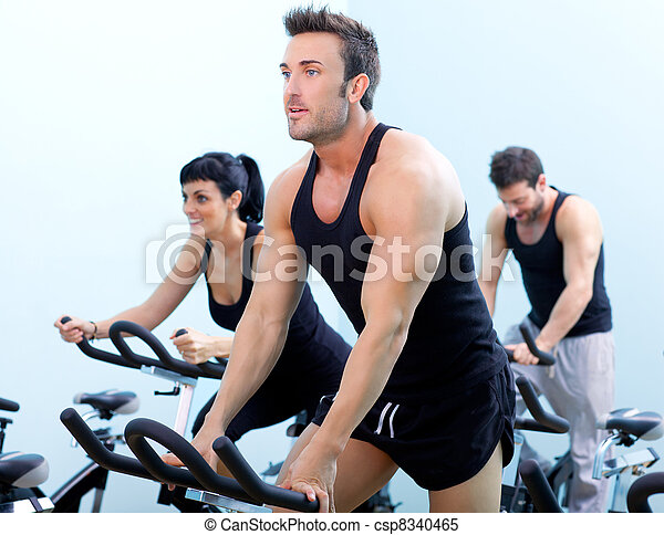 Stationary spinning bicycles fitness man in a gym sport club - csp8340465