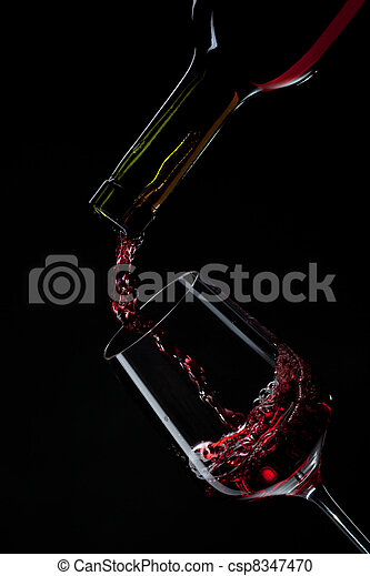 red wine pouring into wine glass isolated on black - csp8347470