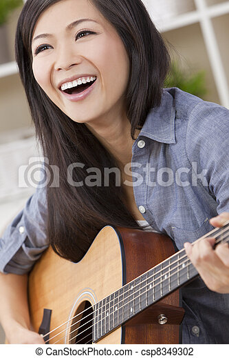 Beautiful Happy Chinese Oriental Asian Woman Smiling & Guitar - csp8349302