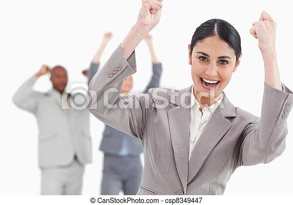 Triumphant businesswoman with cheering associates behind her - csp8349447