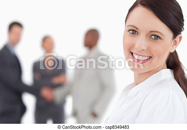 Smiling businesswoman with three associates behind her - csp8349483