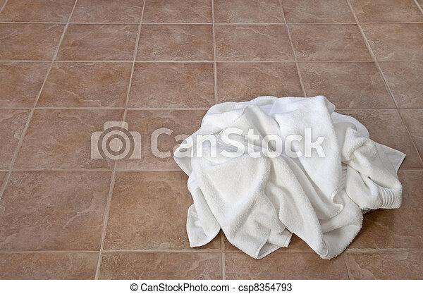 Creased white towels on ceramic floor - csp8354793