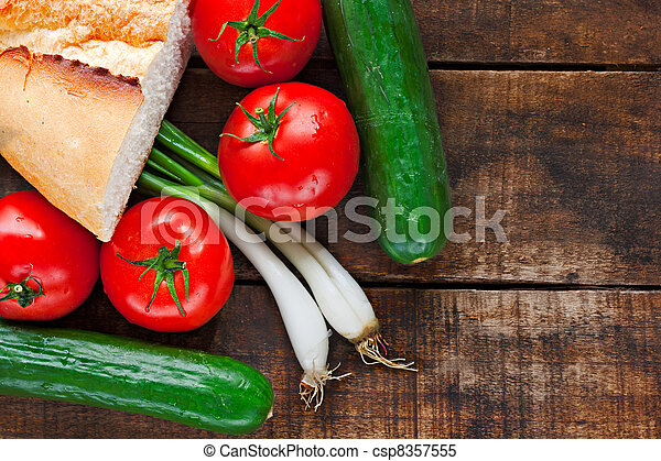 Tomatoes, cucumber, bread and spring onions on old wooden table - csp8357555