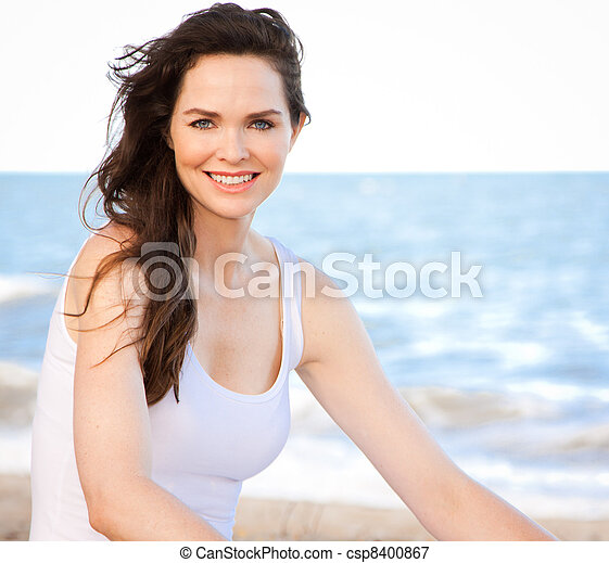 Beautiful healthy woman sitting on beach - csp8400867
