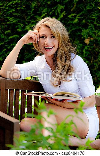 woman reading a book in the garden - csp8404178