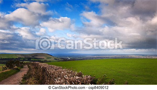 Stunning moody sky with beautiful cloud formations and colors over countryside landscape of path leading into distance - csp8409012