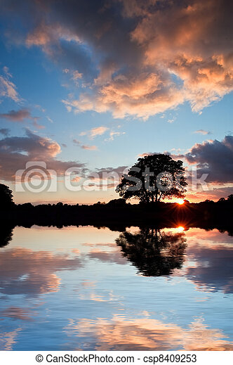 Stunning sunset silhouette reflected in calm lake water - csp8409253