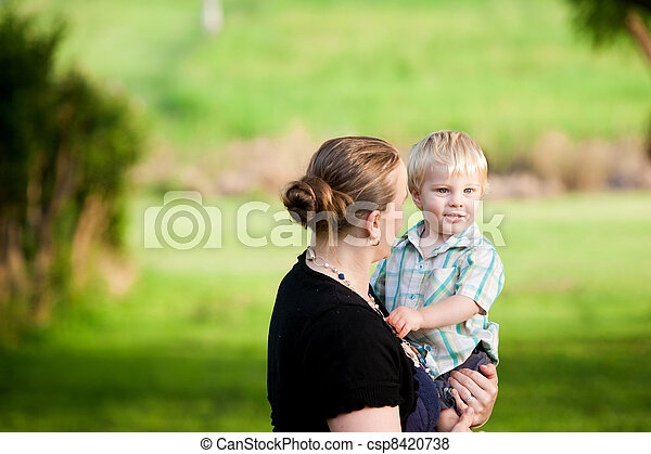 A mum cuddles her little boy in an outdoor green field. - csp8420738