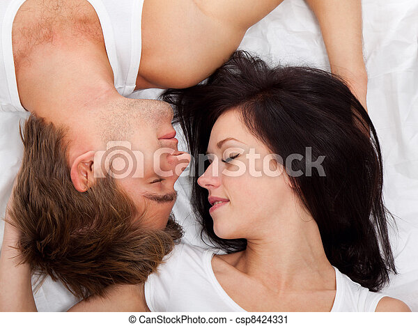 young lovely couple lying in a bed - csp8424331