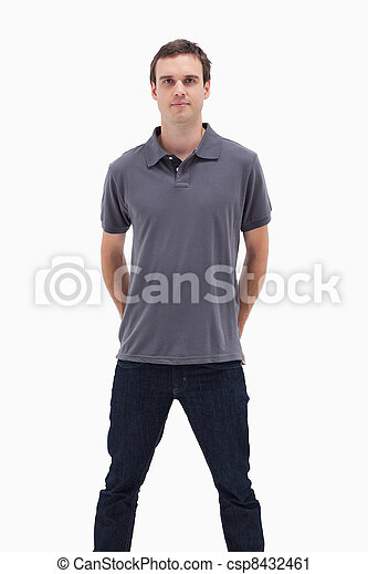 Close-up of a standing man with his hands behind his back and his legs apart against white background - csp8432461