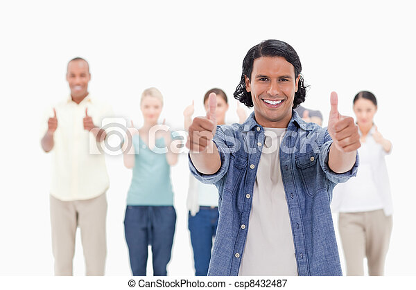Close-up of a man smiling with his thumbs-up with people behind - csp8432487