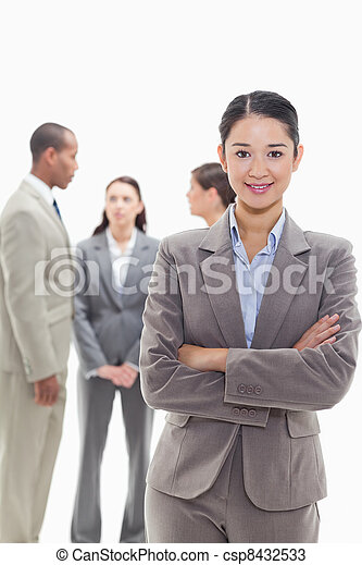 Businesswoman smiling and crossing her arms with co-workers - csp8432533