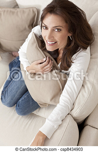 Happy Woman Smiling Hilding Cushion At Home on Sofa - csp8434903