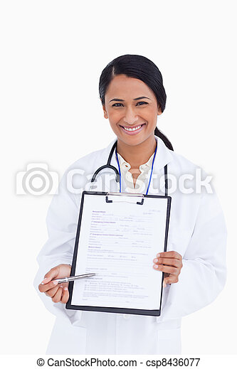 Close up of smiling female physician pointing at form - csp8436077