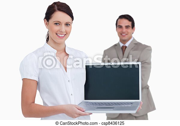 Smiling saleswoman presenting laptop screen with colleague behind her against a white background - csp8436125