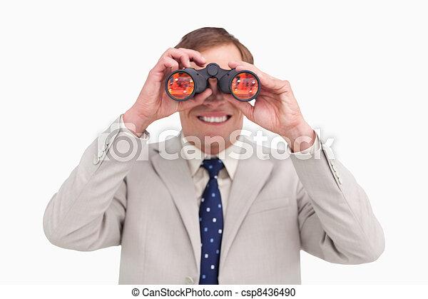 Smiling businessman using binoculars - csp8436490