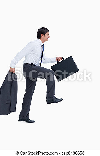 Side view of walking tradesman with jacket and suitcase - csp8436658