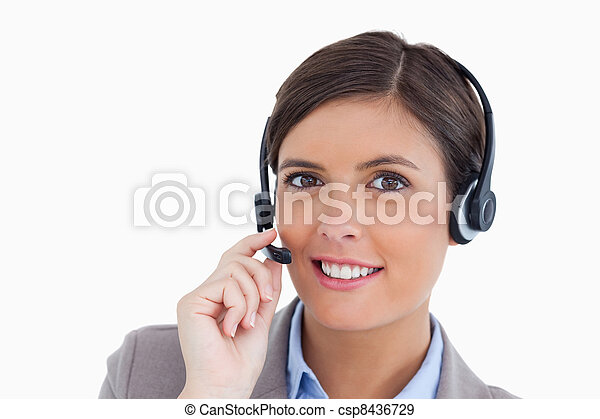 Close up of smiling female call center agent adjusting her headset against a white background - csp8436729