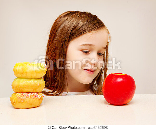 This photo depicts a young girl making decisions betwen healthy y food and unhealthy food. - csp8452698