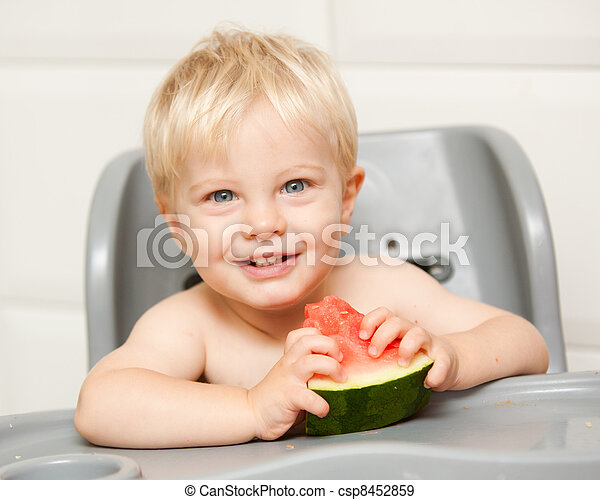 This photo is of a adorable little one year old boy eating watermelon in his high chair at home.  He is definitely enjoying himself. - csp8452859