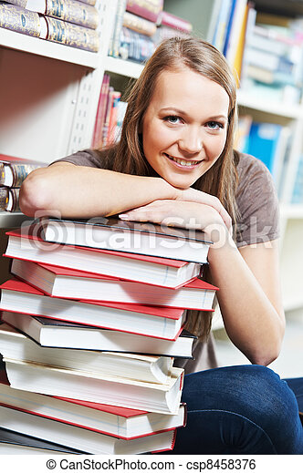 Smiling young adult woman reading  book in library - csp8458376