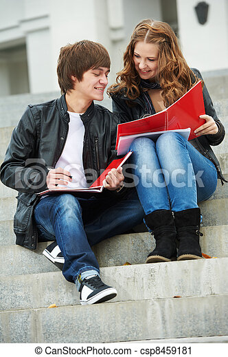 Two smiling young students studying outdoors - csp8459181