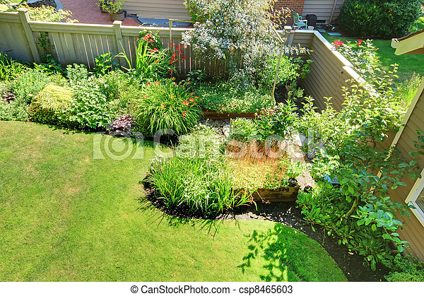 Stock Photos of Fenced back yard corner with flowers and ...