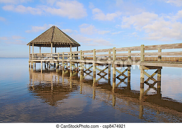 Gazebo, dock, blue sky and clouds over calm sound waters - csp8474921