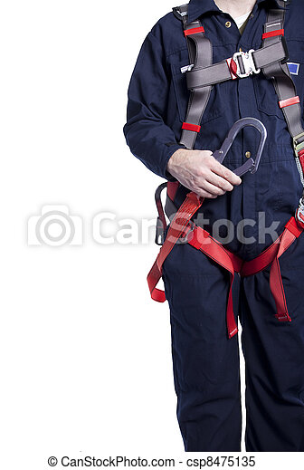 man wearing coveralls and fall protection harness and lanyard - csp8475135