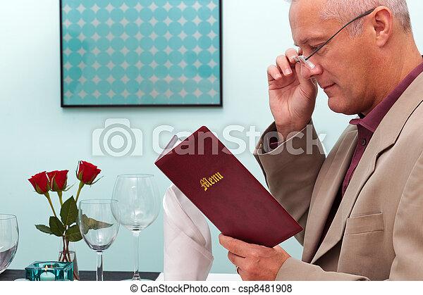 Man reading a menu in a restaurant - csp8481908