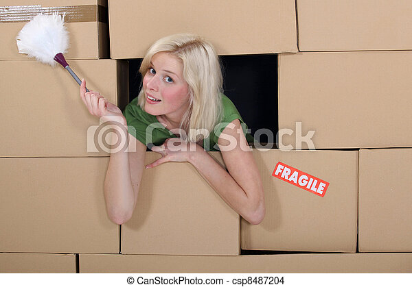 Woman with a feather duster surrounded by packing boxes - csp8487204
