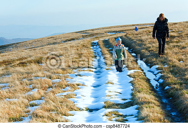 Family walk on autumn  mountain plateau with first winter snow - csp8487724