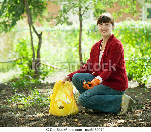 woman fertilizes the soil  - csp8489074