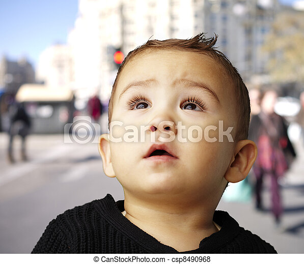 portrait of a handsome kid looking up against at crowded street - csp8490968