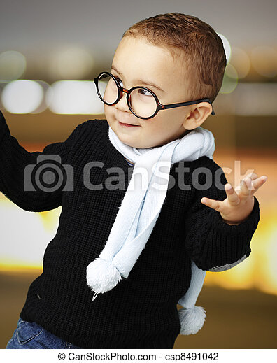portrait of adorable kid wearing glasses gesturing doubt at city - csp8491042