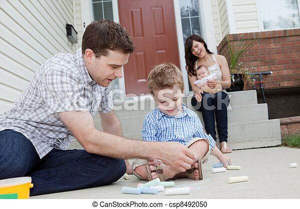 Father And Son Drawing With Chalk on Sidewalk - csp8492050