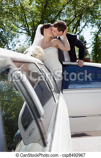 Newlywed Couple Standing Beside Limousine - csp8492967