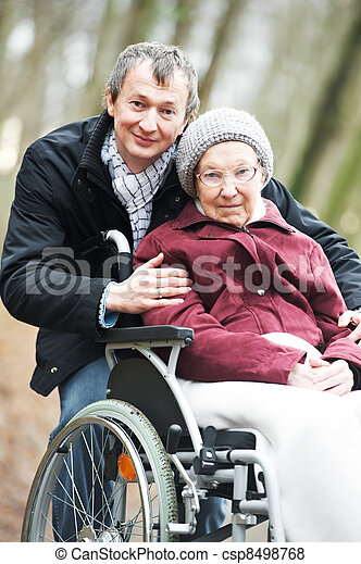 old senior woman in wheelchair with careful son - csp8498768