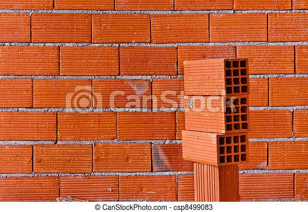 Brick wall with a stack of new bricks